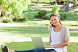 Smiling woman sitting on the grass with her laptop