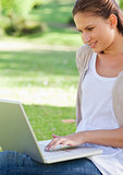 Smiling woman using her laptop while sitting on the lawn