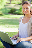 Smiling woman working on her laptop in the park
