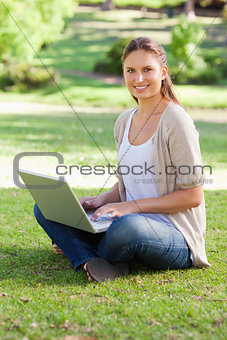 Smiling woman working on her notebook in the park