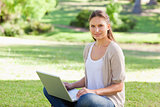 Woman with her laptop sitting on the grass
