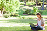 Woman sitting on the lawn working on her notebook