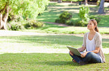 Woman sitting on the meadow with her notebook