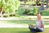 Woman with her laptop sitting in the park