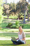 Smiling woman sitting on the lawn with her laptop