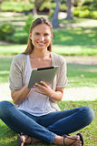 Smiling woman sitting on the lawn with her tablet computer