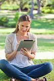 Woman sitting on the grass while using her tablet computer
