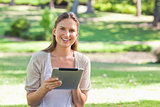 Smiling woman in the park with her tablet computer