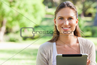 Smiling woman sitting on the lawn with a tablet computer