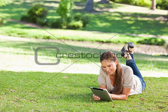 Smiling woman lying on the lawn with a tablet computer