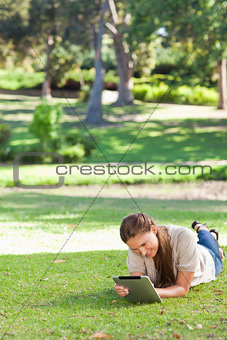 Woman laying on the lawn using a tablet computer