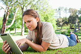 Woman with a tablet computer lying on the lawn