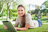Smiling woman with her tablet computer lying on the lawn