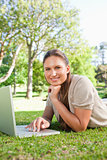 Smiling woman with her laptop while lying on the lawn