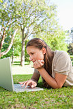 Woman lying on the lawn while using her laptop
