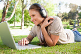 Woman with a laptop and a headset lying on the lawn