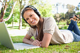 Smiling woman with a headset and a laptop lying on the lawn