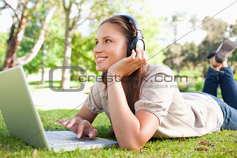 Smiling woman with headphones and a laptop lying on the lawn