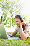 Woman with headphones and a laptop lying on the lawn
