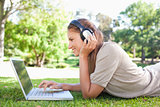 Side view of a woman with headphones and a laptop on the lawn