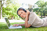 Side view of a smiling woman with headphones and a laptop lying