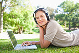 Side view of a woman with her laptop and headphones lying on the