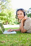 Side view of a woman lying on the lawn with laptop and headphone
