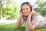Woman with headphones lying on the lawn