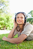 Woman with headphones lying on the grass