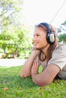 Side view of a woman listening to music on the lawn