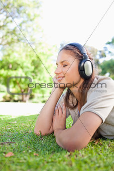 Side view of a woman enjoying music on the lawn