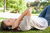 Woman lying on the lawn while enjoying music