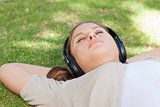 Relaxed woman lying on the lawn enjoying music