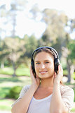Smiling woman in the park wearing headphones