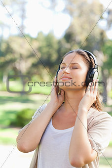 Woman with headphones enjoying music in the park
