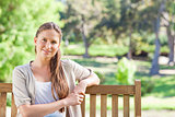 Relaxed woman sitting on a park bench