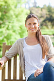 Smiling woman enjoying her day on a park bench