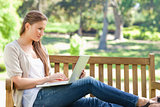 Woman on a park bench working on her laptop