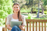 Smiling woman with a tablet computer on a park bench