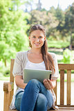 Smiling woman on a park bench with a tablet computer