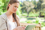 Woman with her tablet computer sitting on a park bench