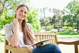 Smiling woman on a park bench with her tablet computer