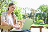 Woman with a laptop on a park bench