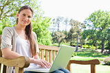 Smiling woman with a laptop on a park bench