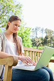 Woman on a park bench with her laptop