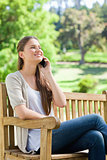 Smiling woman sitting with her cellphone on a park bench