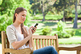 Woman writing a text message on her cellphone while on a park be
