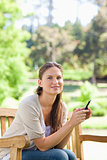 Smiling woman holding her cellphone while on a park bench