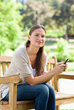 Woman with her cellphone sitting on a park bench