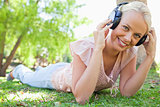 Smiling woman enjoying music on the grass